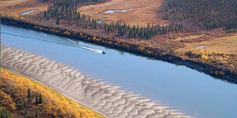A boat speeding along the mighty Kobuk River in Kobuk Valley National Park